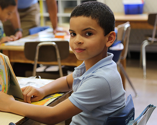 Grade school boy smiling while at his classroom desk